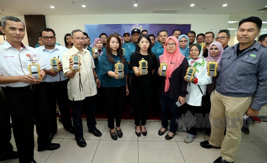 Yeo Bee Yin (tengah) menunjukkan alat pengesan gas di udara di Pasir Gudang Sabtu lalu. FOTO Mohd Azren Jamaludin