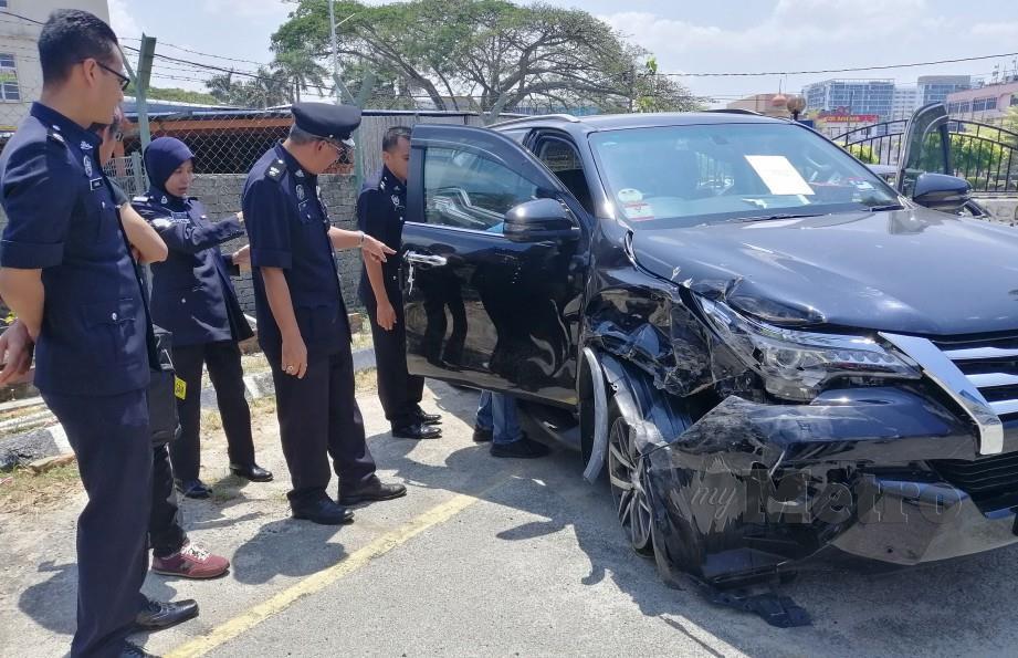 Aidi Sham (dua kanan) melihat Toyota Fortuner milik ahli perniagaan yang dicuri pada ketika sidang media di IPD Port Dickson. FOTO Mohd Khidir Zakaria.