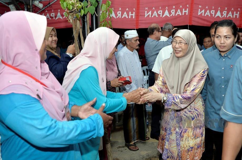 Dr Wan Azizah beramah mesra dengan hadirin ketika membuat lawatan di Kampung Sri Lalang hari ini. FOTO Bernama