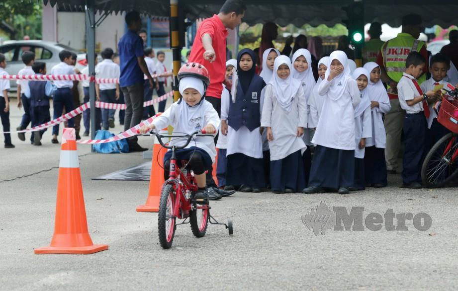 KAKITANGAN JKJR memberi penerangan mengenai cara menunggang basikal yang betul. FOTO Zulkepli Osman.