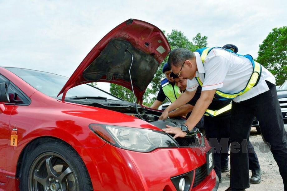 Zulkarnain memeriksa enjin kereta dalam Ops Tutup hari ini. FOTO Rosli Ilham
