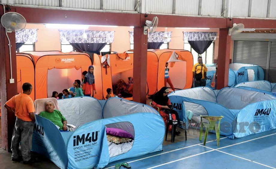 PENDUDUK Kampung Petani Merbau Kudung di pusat pemindahan sementara Dewan Muhibah Merbau Kudung, kelmarin, berikutan rumah mereka dilanda banjir.Seramai 14 keluarga mangsa banjir ditempatkan di pusat berkenaan. FOTO Bernama