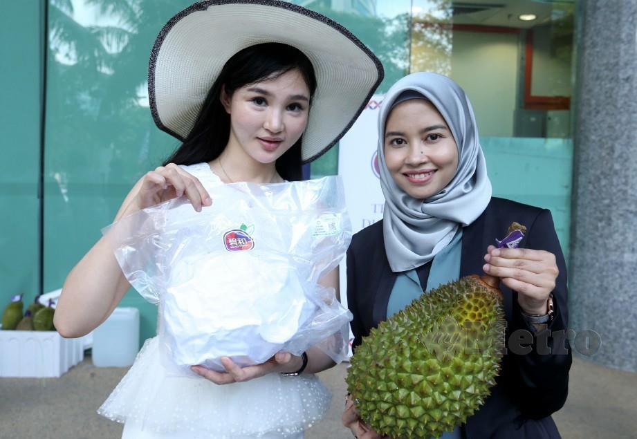 NUR Alifah Najwa Ramli bersama He Yuhan (kiri) menunjukkan durian sejuk beku pada majlis pelancaran durian Musang King sejuk beku dalam bentuk biji di eksport ke China. FOTO Ahmad Irham Mohd Noor