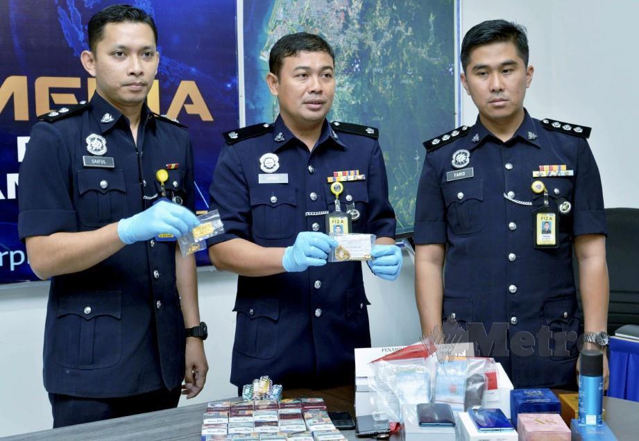 Mohd Haris (dua dari kiri) menunjukkan antara barangan yang dirampas polis termasuk ganja. FOTO Fardy Bungga