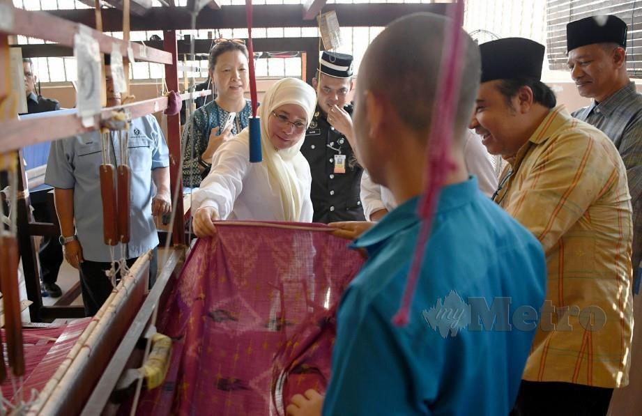 TUNKU Azizah (tengah) berkenan meneliti kain tenun yang sedang disiapkan banduan ketika berangkat bagi melawat Bengkel Tenun Pahang DiRaja Penjara Penor, baru-baru ini. FOTO BERNAMA.