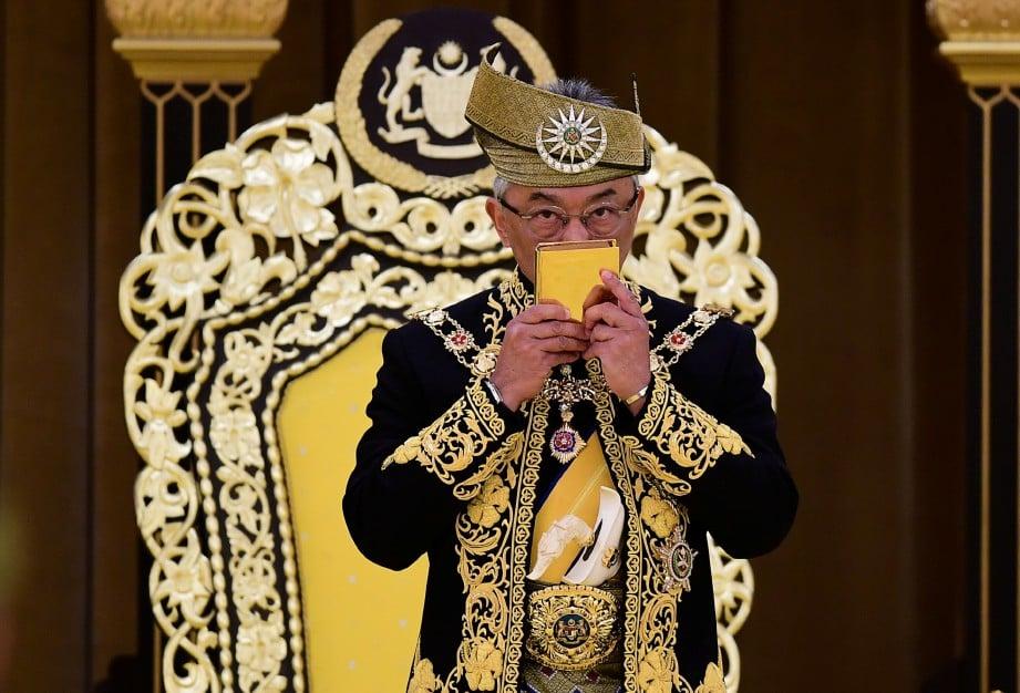AL Sultan Abdullah mencium naskhah aL-Quran yang melambangkan kemuliaan Islam ketika Istiadat Pertabalan Yang di-Pertuan Agong ke-16. FOTO AFP.