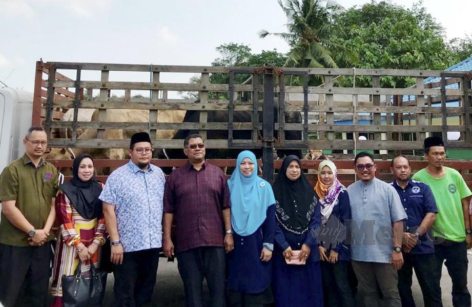 DZULKEFLY (empat kiri) bersama Syarul Izam (tiga kiri) dan penduduk Kampung Tanjung Kupang selepas majlis penyerahan lembu korban. FOTO Mary Victoria Dass
