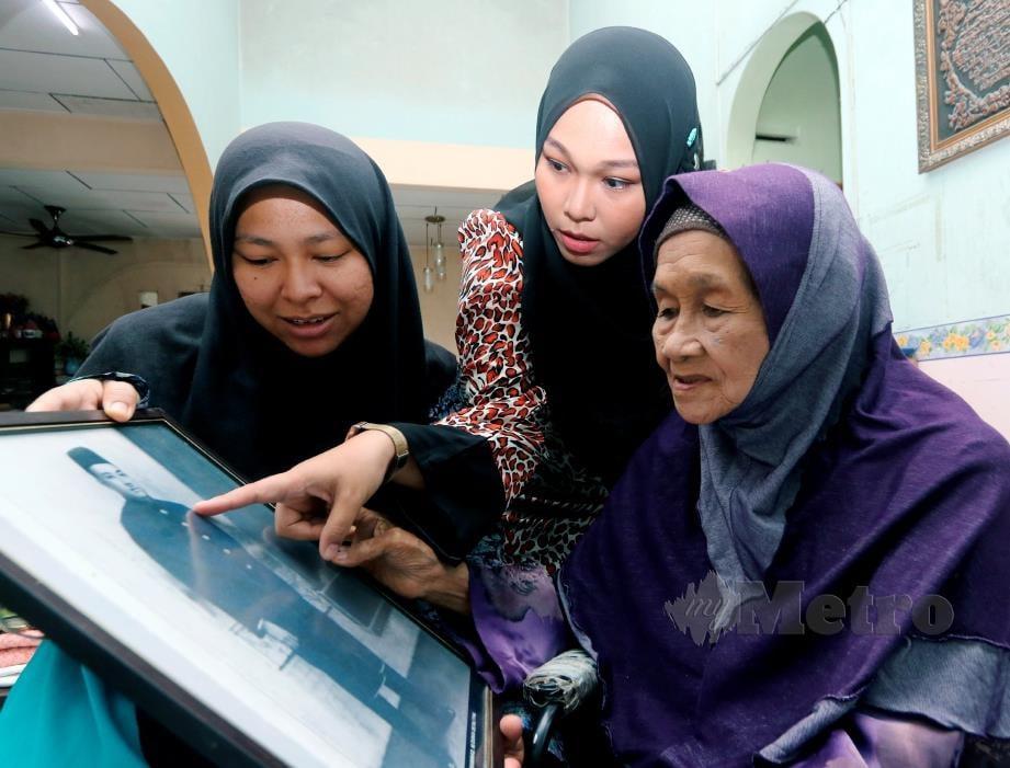MAK Itam (kanan) menatap potret bapanya Sulong Mohamad sambil menceritakan peristiwa berdarah kepada cucunya Syairah Suhaimi, 34, (tengah) dan Suriani Suhaimi, 36, (kiri) ketika ditemui di rumahnya di Sungai Udang. FOTO Bernama