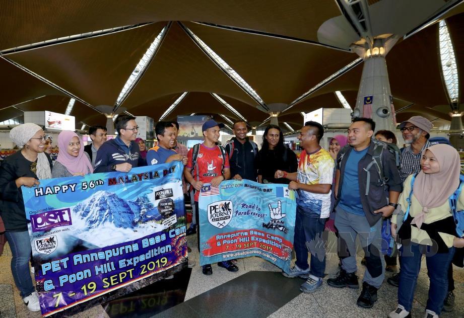 AZIM (empat kanan) beramah mesra dengan Muhammad Hawari (enam dari kiri) dan peserta lain di Lapangan Terbang Antarabangsa Kuala Lumpur. FOTO Ahmad Irham Mohd Noor