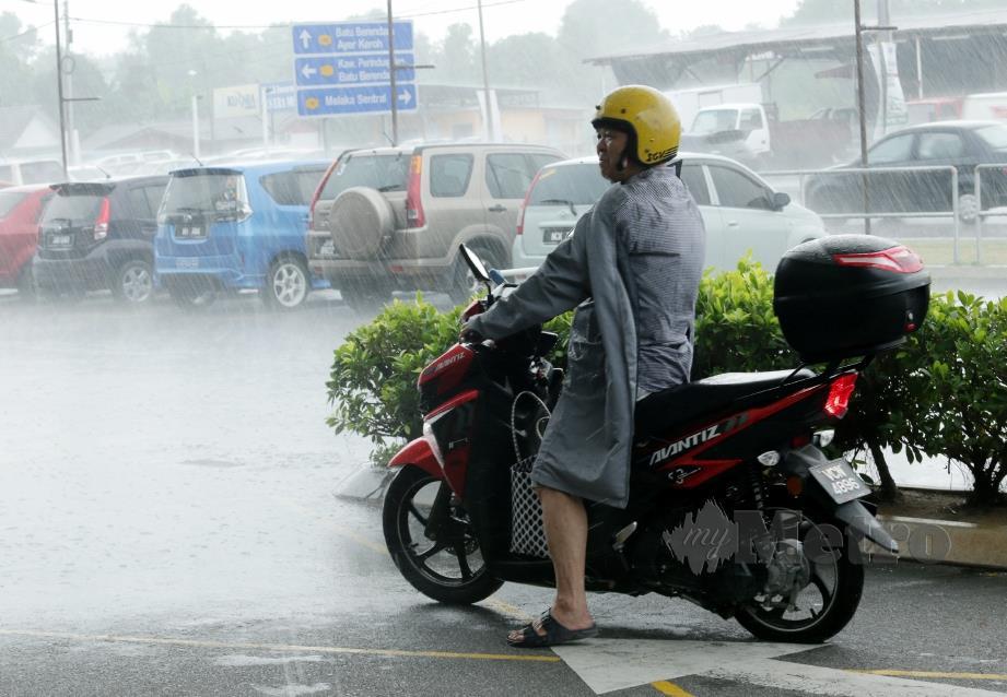 PENUNGGANG motosikal berteduh untuk mengelak daripada dibasahi hujan. FOTO Khairunisah Lokman
