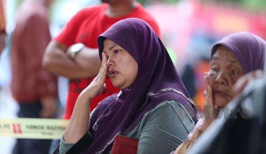 Nurhayati menanti operasi mencari dan menyelamat anaknya di Sungai Terengganu. FOTO Imran Makhzan