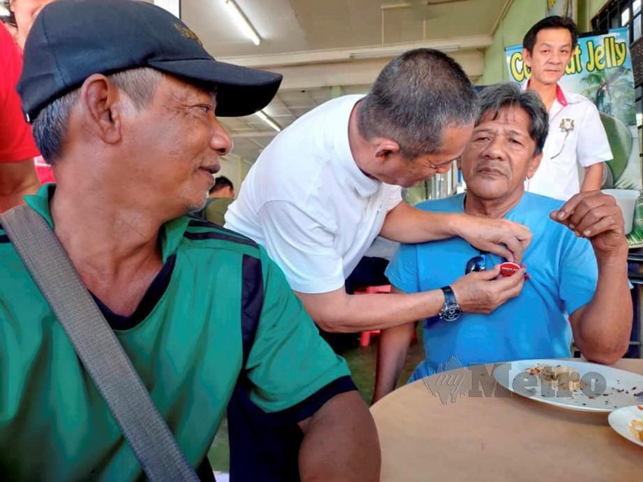 Karmaine memasang lencana PH pada baju penyokong BN ketika kempen di pekan Kukup. FOTO Mohd Sabran Md Sani