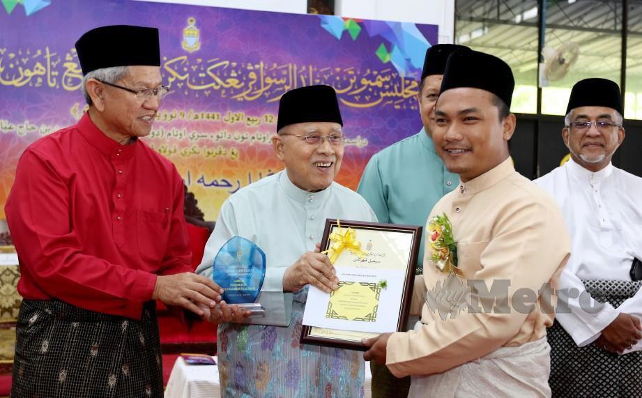 ABDUL Rahman (dua kiri) menyampaikan Anugerah Qudwatur Rasul Shabab kepada Nor Qaiyum (kanan). FOTO Mikail Ong