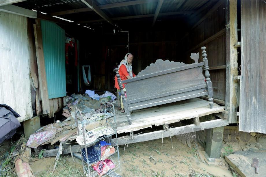 PENDUDUK, Rosahaidah Yaacob, 44, melihat rumahnya dilanda banjir di Kampung Chuchoh Puteri, Kuala Krai, Rabu lalu. FOTO Syamsi Suhaimi