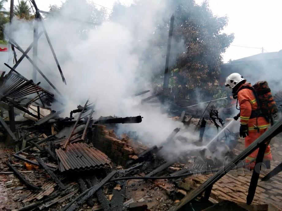 Anggota bomba memadamkan kebakaran rumah kayu di RKT Kesedar Paloh 3. FOTO Ihsan JBPM