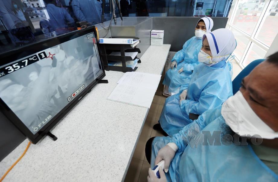 KAKITANGAN kesihatan memantau keadaan orang ramai dengan mengunakan mesin pengimbas suhu badan  di pintu masuk Kompleks Kastam, Imigresen, Kuarantin dan Keselamatan (ICQS) Bukit Kayu Hitam, minggu lalu. FOTO AMRAN HAMID