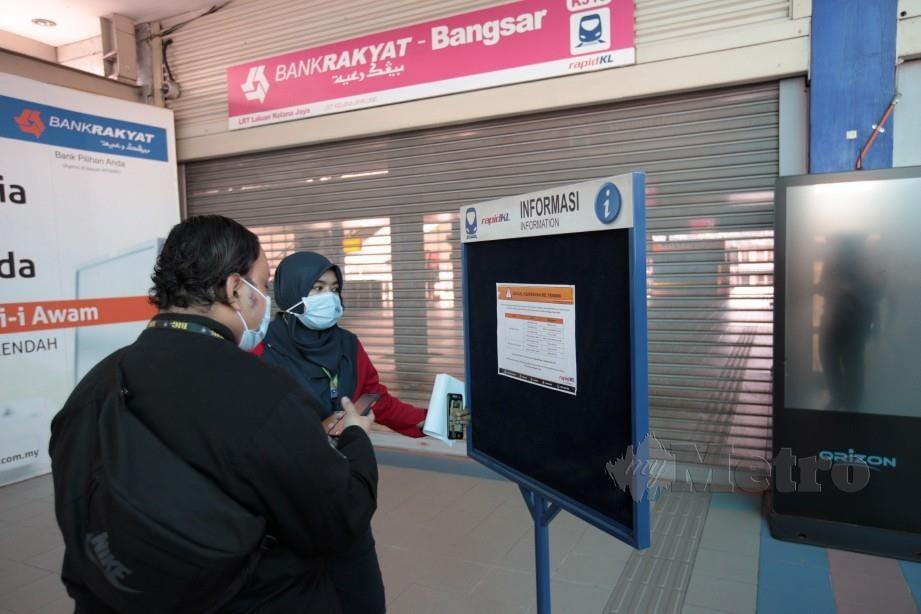 KAKITANGAN LRT laluan Kelana Jaya, Hayati Malek memberi penerangan kepada penumpang berkenaan jadual di stesen LRT Bangsar selepas ditutup tepat pada 10 pagi bagi mematuhi Perintah Kawalan Pergerakan. FOTO Asyraf Hamzah