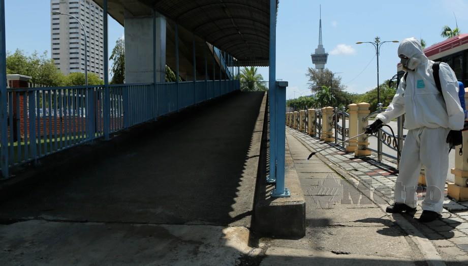 PETUGAS Majlis Perbandaran Kuantan (MPK) melakukan proses dan kerja nyah cemar serta sanitasi di kawasan tumpuan orang awam di sekitar bandar Kuantan bagi mencegah penularan wabak Covid-19, kelmarin. FOTO Farizul Hafiz Awang