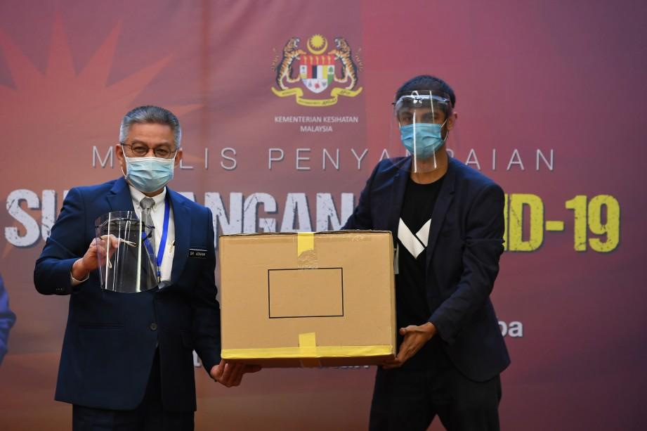DR Adham  (kiri) menerima sumbangan pelindung muka dari Me.Reka Innovative Education. FOTO Bernama.