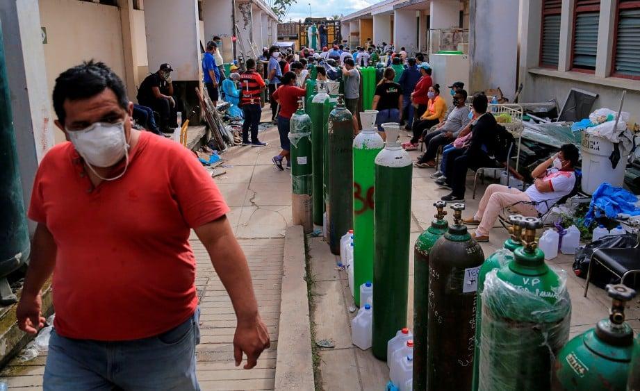 SAUDARA mara pesakit Covid-19 beratur untuk mengisi semula tangki oksigen di sebuah hospital di Iquitos. AFP
