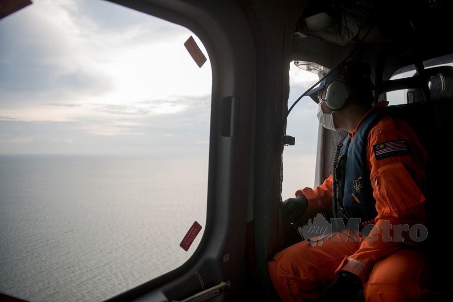 PEMERHATI Udara PGU, Lans Koperal Mohammad Al- Amin Abdul Rahim melihat keadaan semasa di perairan Selat Melaka ketika tinjauan udara. FOTO Bernama