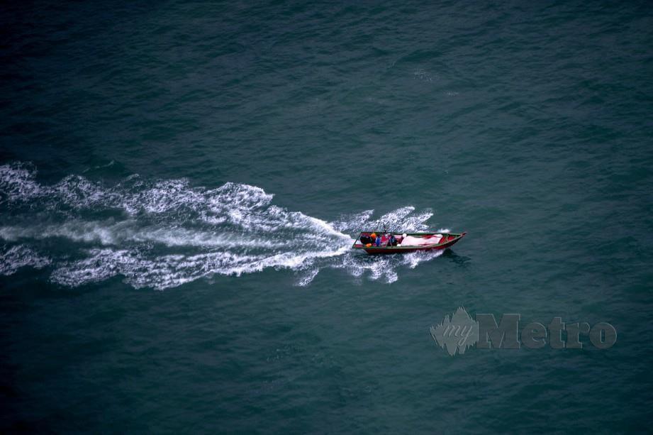 KELIHATAN bot nelayan di perairan Selat Melaka ketika tinjauan udara bersama PGU PDRM. FOTO Bernama