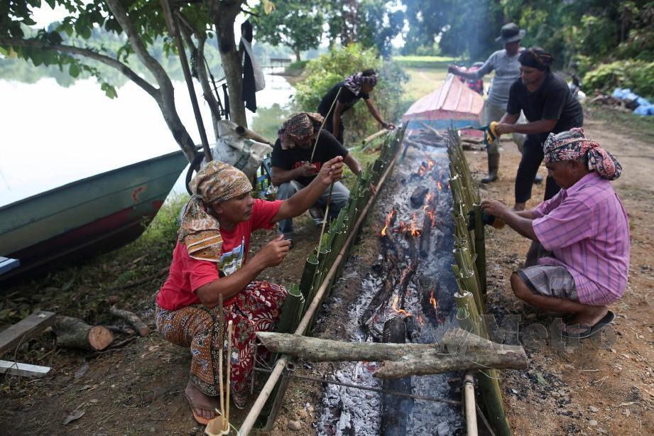 Penduduk bergotong royong membakar lemang di Kampung Pulau Manis, Serada. FOTO GHAZALI KORI