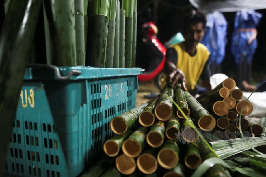 Penduduk memasukkan daun tebu ke dalam buluh lemang. FOTO GHAZALI KORI