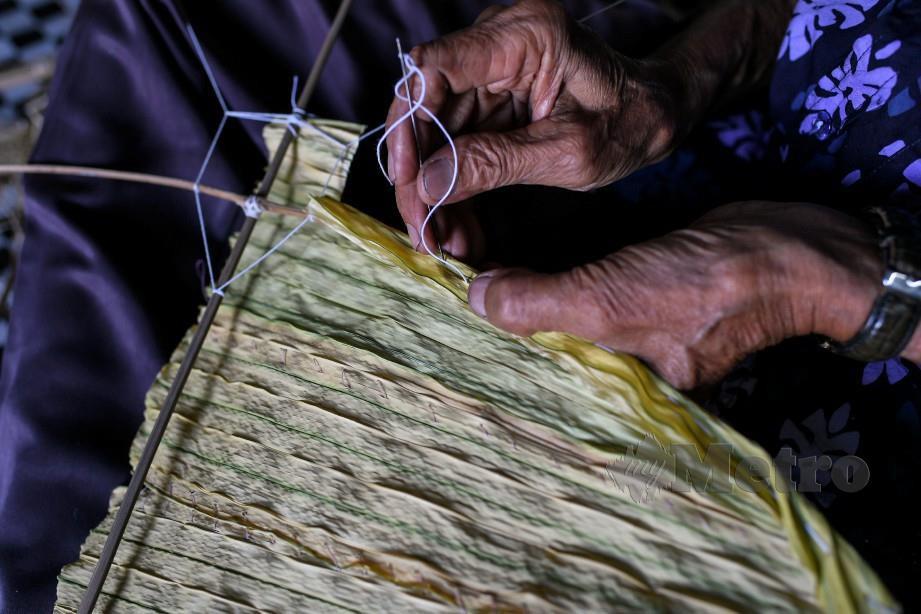 PAK Non menjahit daun palas pada rangka badan Wau Helang. FOTO Bernama