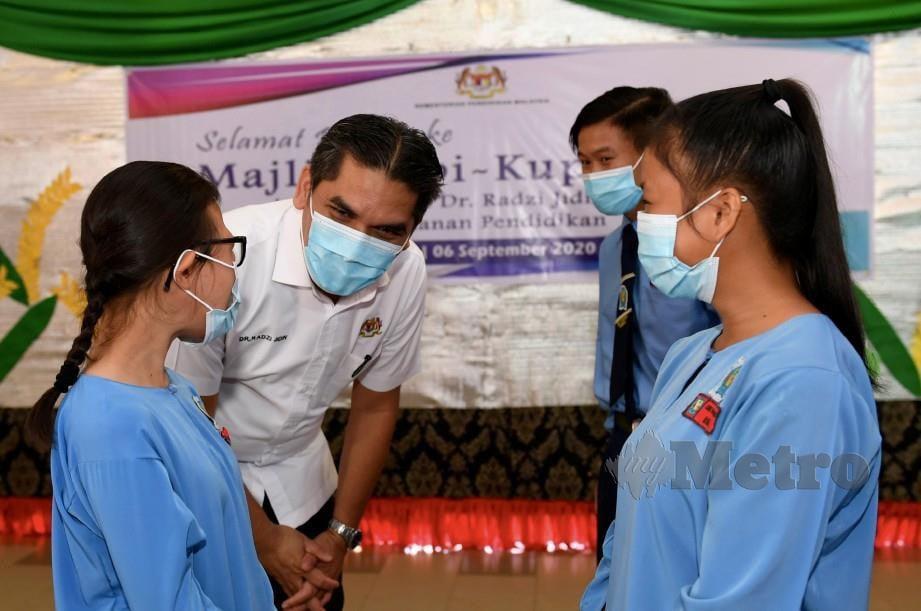 RADZI memperkatakan sesuatu kepada pelajar pendidikan khas SMK Nambayan Tambunan. FOTO Bernama