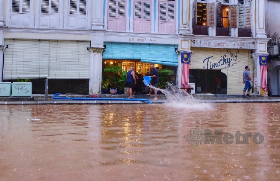 Peniaga mengeluarkan air dari dalam kedai mereka selepas dilanda banjir kilat di Jalan Hang Lekir akibat hujan lebat di ibu kota. FOTO MOHD YUSNI ARIFFIN