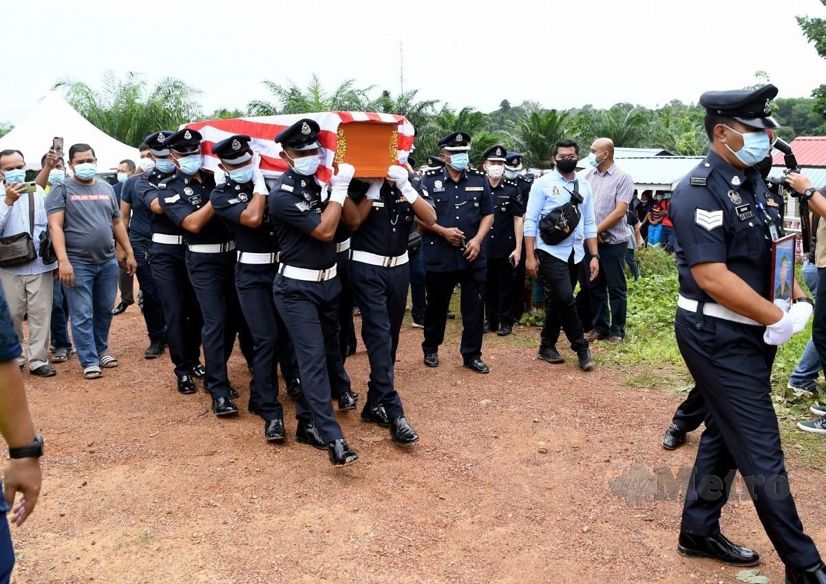 ANGGOTA polis mengusung keranda mendiang Baharuddin dengan penuh istiadat Polis Diraja Malaysia (PDRM) untuk disemadikan di Tanah Perkuburan Orang Asli Kampung Sungai Sampo. FOTO BERNAMA