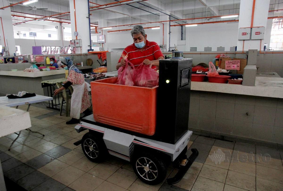 PENIAGA ayam, Mohd Jamil Jamlus 49, mencuba menggunakan perkhidmatan robot mengangkut barang yang kini sedang diuji dan akan beroperasi sepenuhnya pada 15 Disember ini di Pasar Ayam Ipoh. FOTO BERNAMA