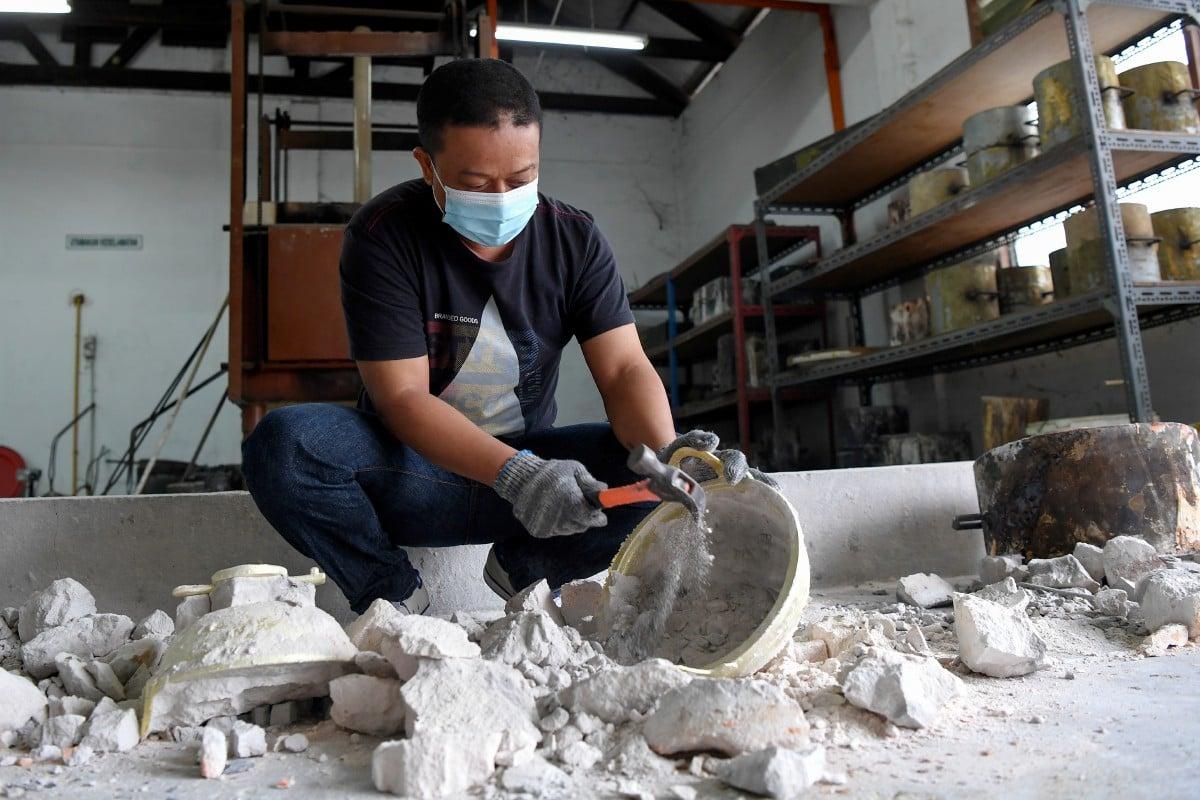SHAIFUL melakukan proses memecahkan acuan bagi mengeluarkan periuk tembaga separa siap. FOTO Bernama