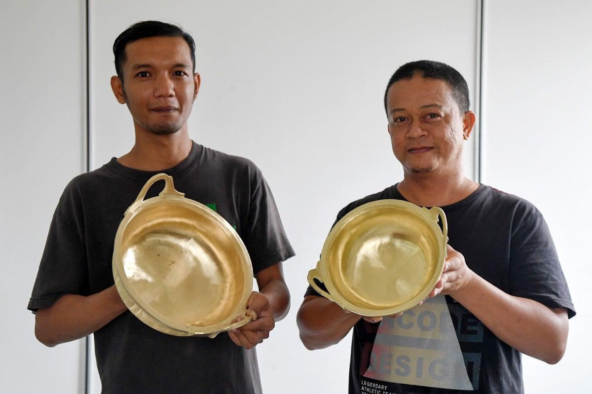 SHAIFUL (kanan) dan Azuan menunjukkan periuk tembaga yang dihasilkan oleh syarikat mereka. FOTO Bernama