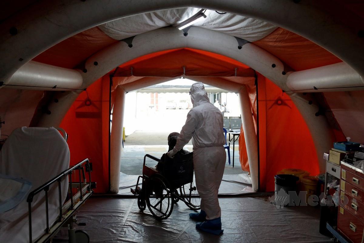 KAKITANGAN Hospital Canselor Tuanku Muhriz UKM menolak pesakit disyaki positif Covid-19 untuk dibawa ke wad bagi rawatan lanjut selepas saringan dan rawatan awal, 12 Jan lalu. FOTO Aizuddin Saad