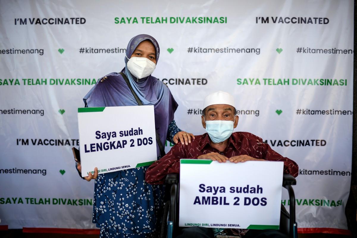 Mohd Khassim bersama anaknya, Nor Asmin selepas selesai menerima suntikan vaksin Covid-19 dos kedua di Jitra. FOTO Bernama