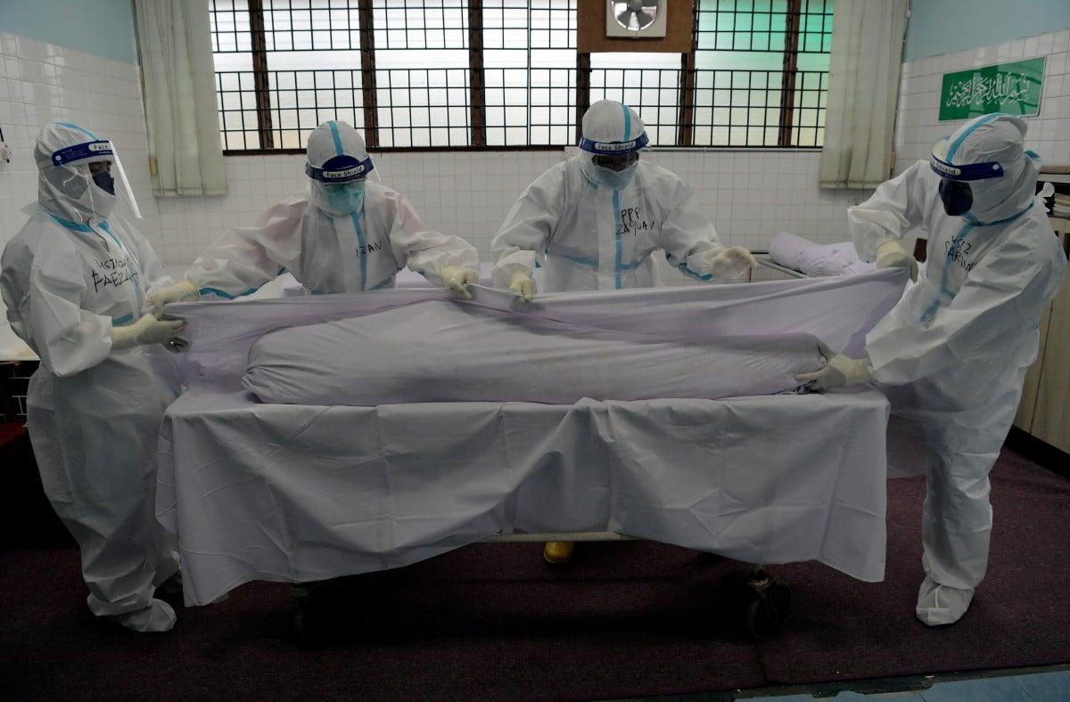 PETUGAS khas pengurusan jenazah Covid-19 mengkafankan jenazah Covid-19 di Jabatan Perubatan Forensik HSA. FOTO Bernama