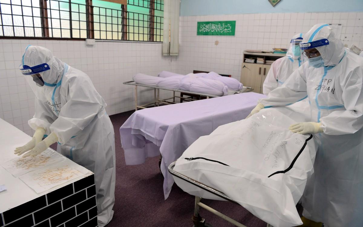 PROSES tayammum dilakukan pada jenazah Covid-19 beragama Islam oleh petugas khas pengurusan jenazah Covid-19 di Jabatan Perubatan Forensik HSA. FOTO Bernama