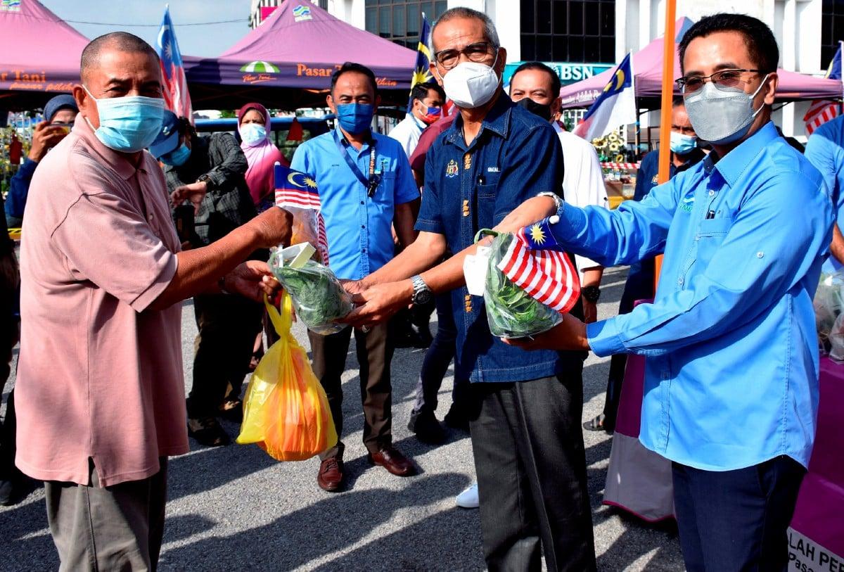 GHAZALE (dua, kanan) menyampaikan sumbangan sayur-sayuran kepada pengunjung di Pasar Tani Jasin. FOTO Bernama