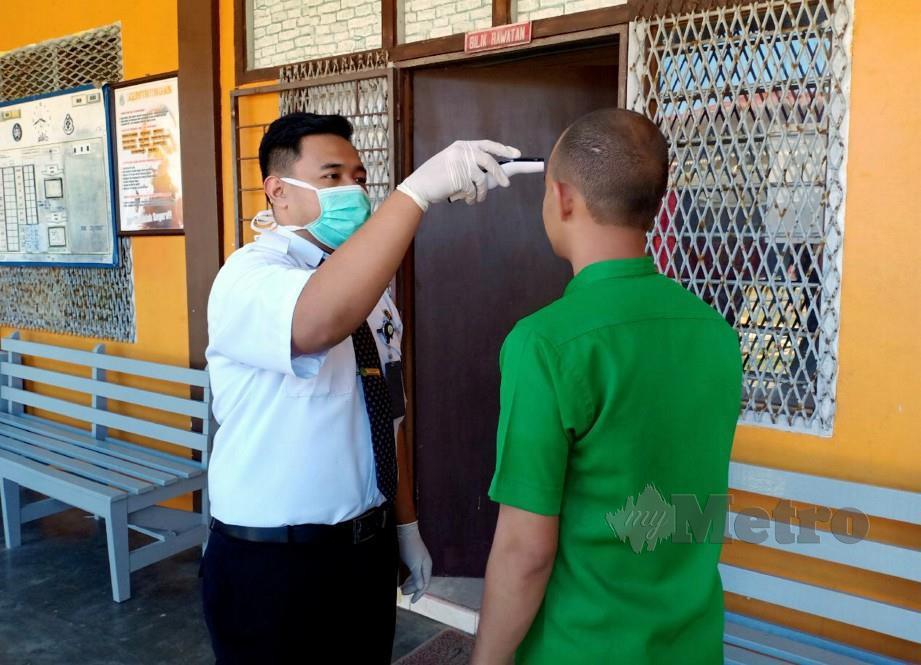 PENOLONG Pegawai Perubatan Penjara Marang sedang memeriksa suhu badan penghuni bagi mencegah penularan Covid-19 di dalam penjara. FOTO AHMAD RABIUL ZULKIFLI