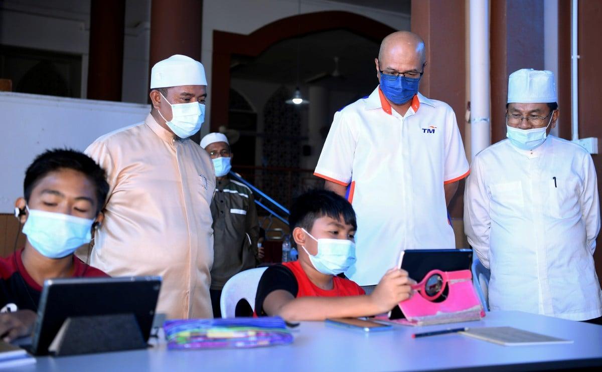 AZHAR (dua dari kanan) Fadzilah (kiri) melihat Muhamad  Faris Danial dan adiknya Muhamad Iman Danial melayari internet yang dibekalkan secara pencuma oleh UNIFI untuk memudahkan golongan kurang berkemampuan belajar secara dalam talian iaitu Pengajaran dan Pembelajaran Dirumah (PdPR) di Masjid Paroi Jaya. FOTO BERNAMA