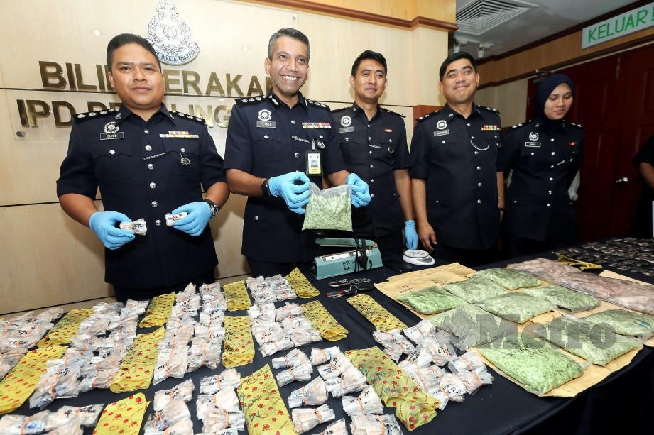 NIK EZANEE (dua dari kiri) bersama anggotanya menunjukkan bungkusan plastik berisi dadah disyaki heroin yang dirampas dari sindiket pengedaran dadah di kawasan pentadbiran IPD Petaling Jaya. FOTO OWEE AH CHUN.