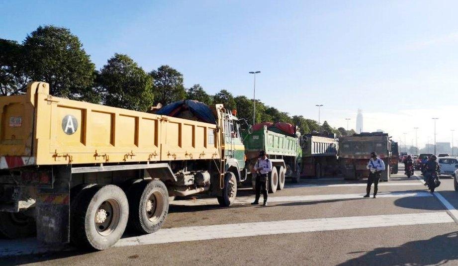 ANGGOTA trafik menjalankan pemeriksaan di Lebuhraya Sultan Iskandar dan Lebuhraya Kuala Lumpur-Seremban, pagi semalam.