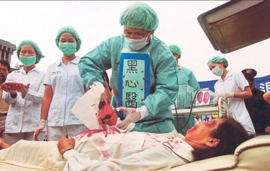 PENGAMAL Falun Gong melakukan protes dengan melakonkan semula cara pengambilan organ daripada tahanan.