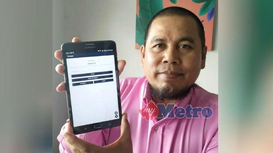 Khairul Hisham menunjukkan aplikasi pembayaran parkir, Padiyo yang menawarkan kredit RM50 secara percuma bermula hari ini sehingga 31 Mac apabila meletakkan kereta di Jalan Seruling. FOTO Muhammad Mustakim Ramli