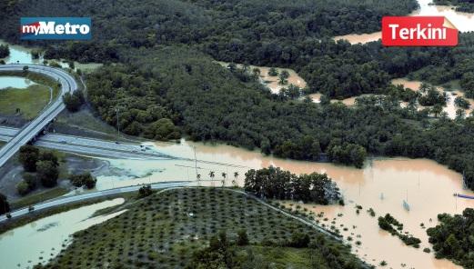 TINJAUAN udara Pahang menunjukkan Lebuhraya Pantai Timur (LPT) masih digenangi air akibat air sungai Pahang yang melimpah. FOTO Bernama