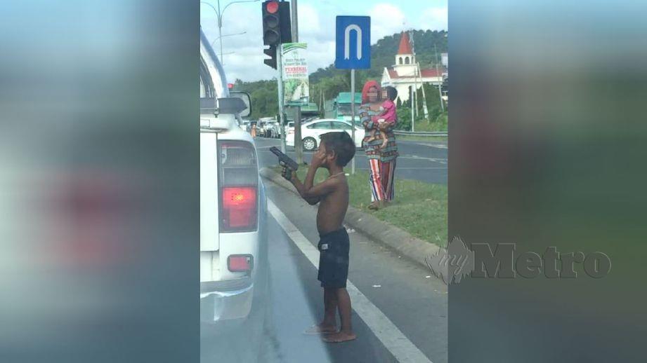 GAMBAR kanak-kanak Palauh mengacukan pistol ketika meminta sedekah. FOTO ihsan pembaca