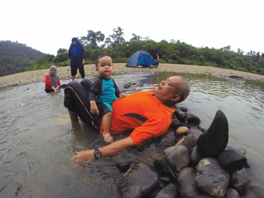 BAPA penulis sedang melayan cucu di tebing sungai Kampung Pasir Kubur.
