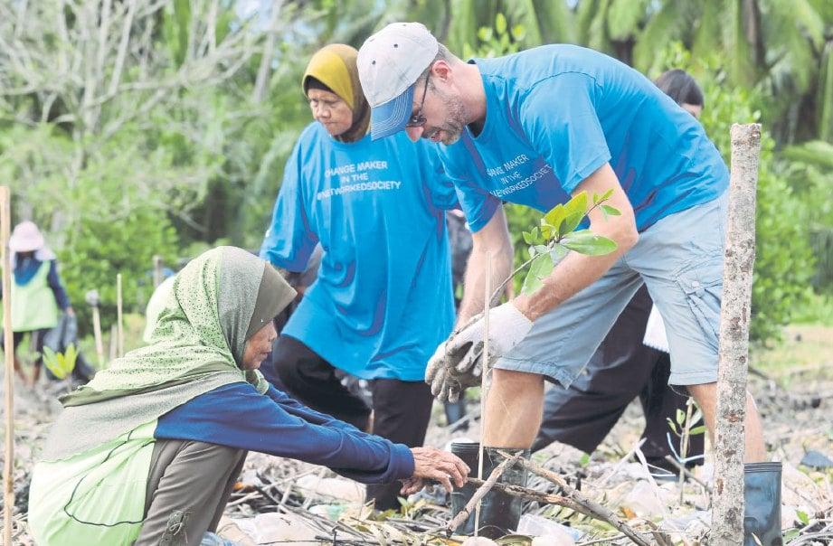 PENDUDUK kampung turut sama menanam anak pokok bakau.